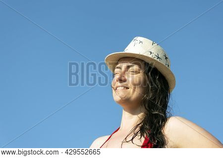 Bottom View Of A Young Woman In A Hat And A Swimsuit Against The Background Of A Blue Sky, A Young W