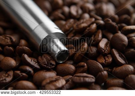 E-cig Device Mod Lies On The Background Of Coffee Beans. Concept Of Vape Coffee Juice