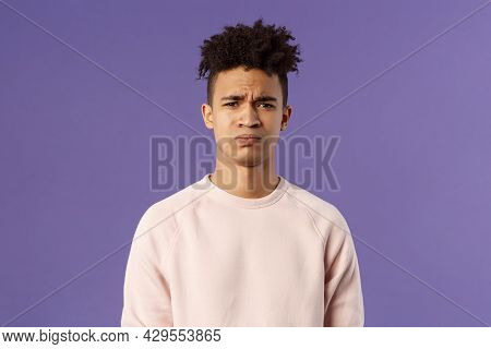 Close-up Portrait Of Skeptical And Gloomy, Disappointed Hispanic Young Man Frowning Upset, Feel Unea