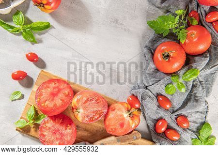 Large Variety Of Tomatoes On Rustic Kitchen Counter. Preparation Of Tomato Sauce With Onions And Bas