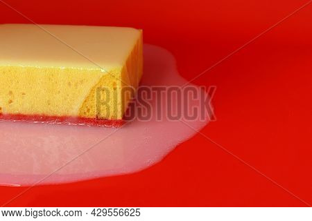 Yellow Sponge On A Red Background, Liquid Soap Spreads On Top Of The Sponge