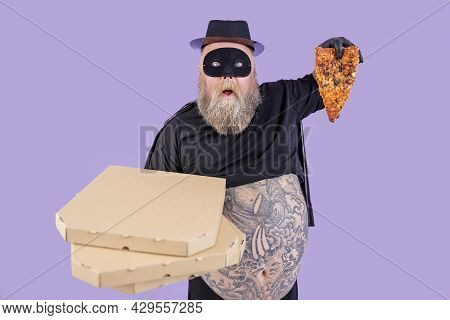Shocked Plump Man In Hero Costume Holds Boxes And Slice Of Pizza On Purple Background