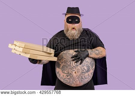 Surprised Plump Person In Zorro Suit Holds Boxes Of Pizza On Purple Background