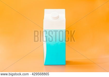White And Blue Cardboard Box Of Milk On A Orange Background. Eco Food. 2 Litres Paper Bottle Of Milk