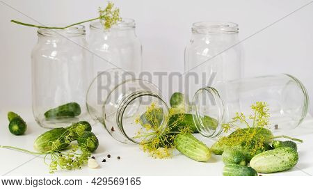 Glass Jars, Fresh Cucumbers, Dill, Garlic And Black Pepper On A White Table On A White Background. I