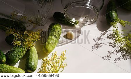 Glass Jars,fresh Cucumbers,dill,garlic And Black Pepper On White Plate,top View,flat Lay,copy Space.