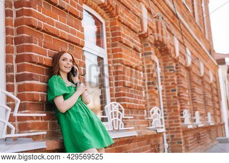 Low-angle View Of Cheerful Young Redhead Woman Talking On Mobile Phone Standing Leaning On Old Red S
