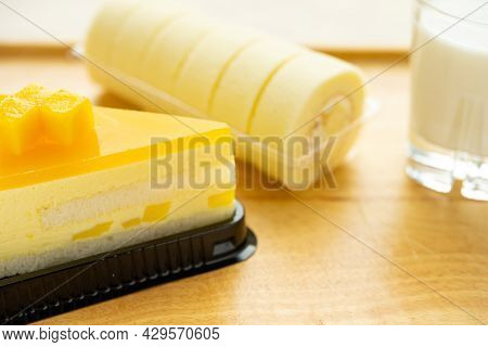 Angle View Fresh Mango Cake And Sweet Rolls With Cup Of Milk Horizontal Composition