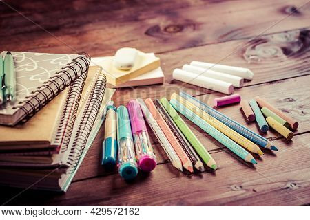 School supplies with exercise book and notepads on wooden background. Back to school concept.