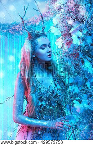 Enchanting horned wood nymph in a magical forest. Fantasy world in light blue and light pink lighting.