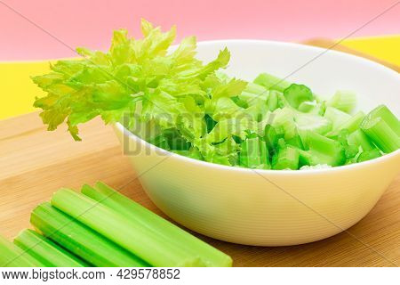Fresh Chopped Celery Slices In White Bowl With Celery Sticks On Bamboo Cutting Board. Vegan And Vege