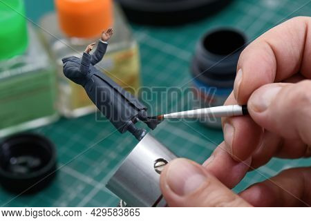 Scale Modeling 1:35. A Man Painting Plastic Wwii Soldier Figure In Uniform. Figure Of A German Soldi