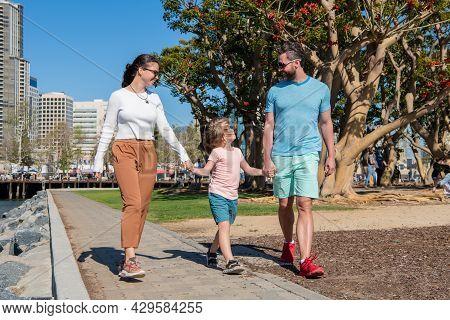Friendly Family Having Fun In Summer. Happy Parents Leading Kid Boy.