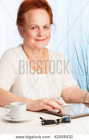 Smiling Old Woman With Tablet Pc