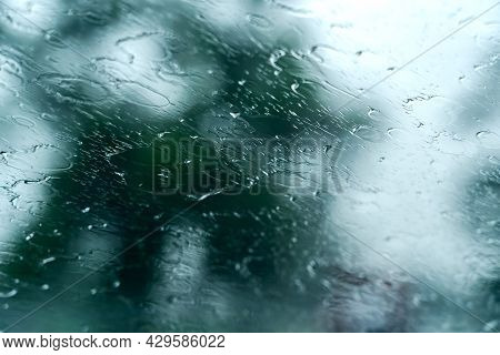 Rain Waters On Glass Of Car Unique Blurry Photo, Traveling Under Rain. Abstract Wet Windshield On Ra