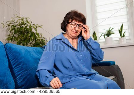 The Tired But Happy Senior Woman Is Sitting On A Sofa
