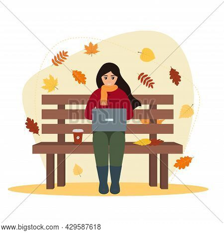 Young Woman Freelancer With Laptop And Coffee Sitting On The Bench In Autumn Nature With Colorful Le