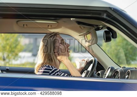 Middle Aged Woman Fixing Makeup Looking In Rear View Mirror Driving Car. Female Driver Distracting F