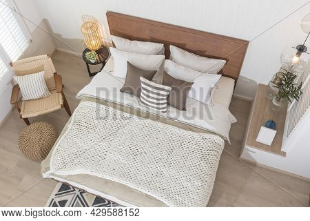 Interior Of Modern Bedroom With White Mattress, Wooden Headboard, Armchair And Small Wardrobe. Top V