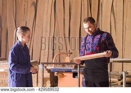 Young Apprentice Learning To Work At Carpentry Shop