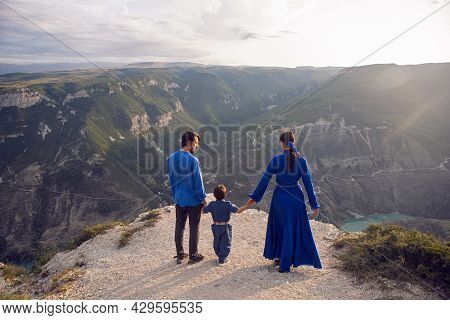 Family Of Three People Stands On The Mountain Gorge During Sunset
