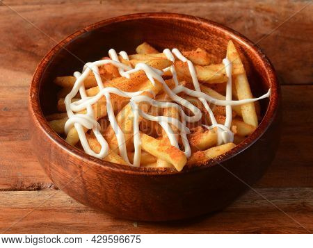 Peri Peri French Fries, Topped With Mayonnaise, Served In A Wooden Bowl Over A Rustic Wooden Backgro