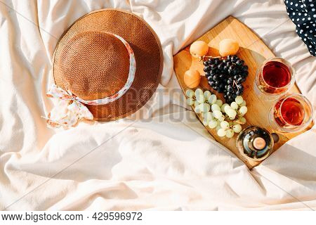 Picnic In Nature. Top View Of Bottle Of Red Wine, Two Glasses Of Alcohol, Grapes, Peaches On Wooden