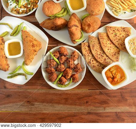 Assorted Indian Tea Time Snacks In Group Includes Spicy Onion Fritters, Bread Pakora,samosa, Kachori