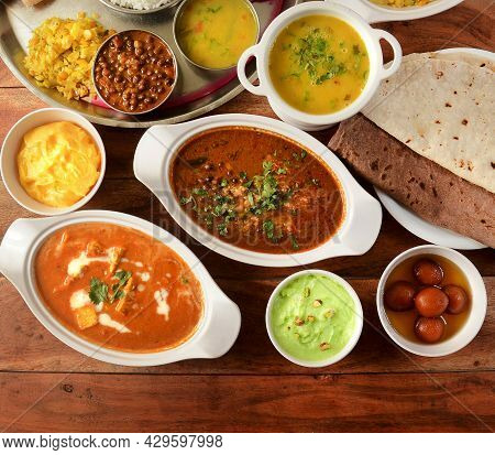 Assorted Indian Foods Paneer Butter Masala,channa Masala,roti And Veg Thali On Wooden Background. Di