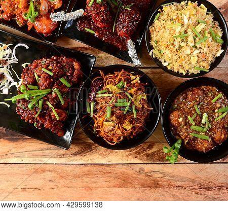 Assorted Indian Food On Wooden Background. Egg Fried Rice,chicken Manchurian,gobi Manchurian,chilli