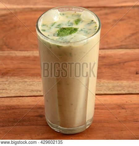 Masala Buttermilk Drink Or Masala Chaas, Made Of Yogurt. Served In A Glass Over A Rustic Wooden Back