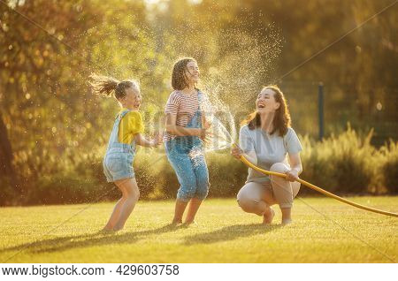 Happy family playing in backyard. Mother sprinkling her kids in hot summer day.