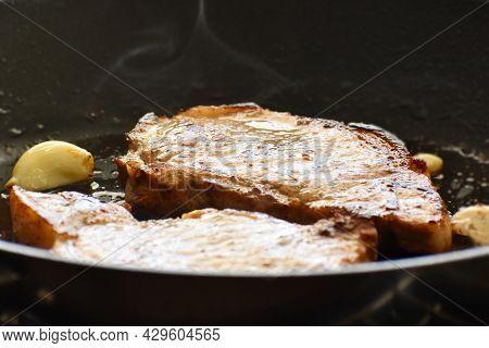 Pork Chop On A Frying Pan. Grilled Pork Steak With Garlic On A Black Metal Pan.