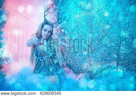Winter fairy tale. Enchanting horned wood nymph in a chic dress in a magical forest. Fantasy world in turquoise and light pink lighting.