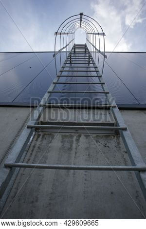 Fire Escape On The Industrial Building Above, Bottom View. Stainless Steel Handrails, Roof Ladder. D