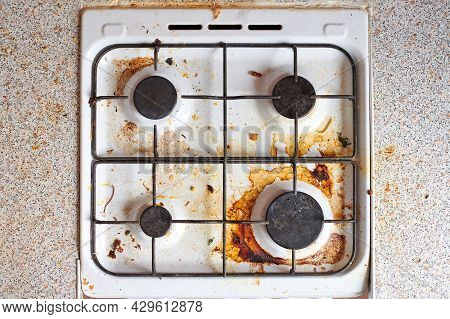 Dirty Grease Stove With Food Leftovers. Unclean Gas Kitchen Cooktop With Greasy Spots, Old Fat Stain