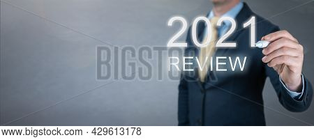 Businessman Writes 2021 Review Words. Businessman Writes 2021 Results On Virtual Screen. Economic In