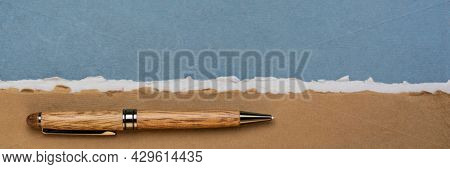 paper abstract in brown and blue with a copy space and a stylish pen - sheets of handmade rag paper, panoramic web banner