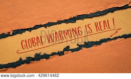 global warming is real - climate emergency concept, handwriting on a handmade orange and black paper