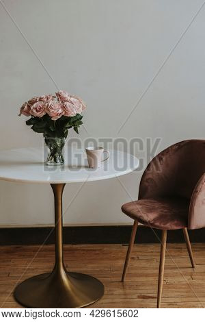 Coffee in a pink cup by a vase of pink roses