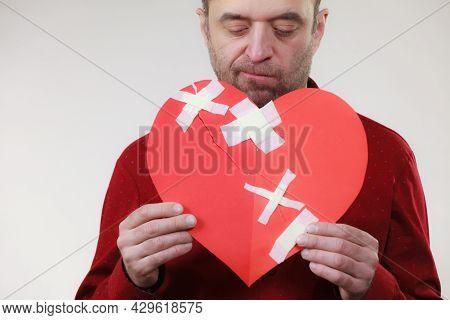 Bad Relationships, Breaking Up, Emotions Concept. Funny Adult Man Holding Broken Heart, On Grey