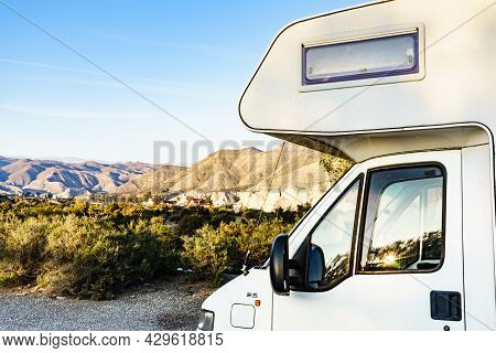 Caravan Vehicle Camping In Tabernas Desert. Western Leone Town In The Distance. Almeria Province, An