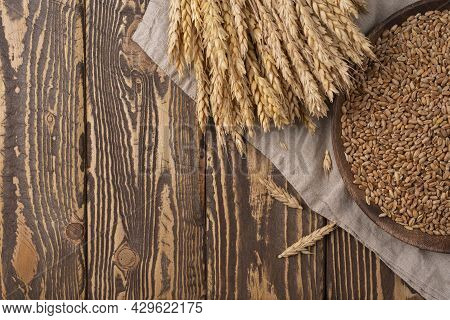 Wheat On The Wooden Table. Sheaf Of Wheat Over Wood Background. Harvest Organic Concept. Wheat With