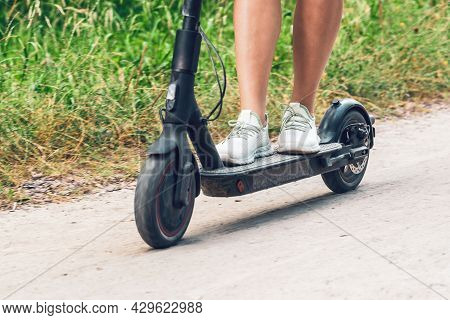 Female Feet On An Electric Scooter Riding On A Dirt Road.