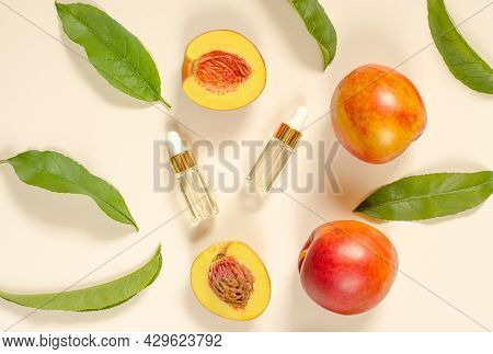 Natural Peach Oil. Two Bottles With Essential Peach Oil, Peaches And Green Peach Leaves On A Beige B