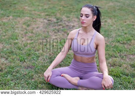 Young Woman In Yoga Lotus Sit Meditating In Garden