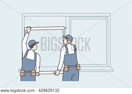 Repairing And Reconstruction At Home Concept. Two Men Workers In Uniform Standing Changing Window Fo