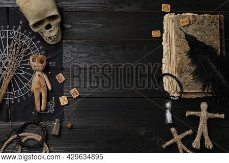 Voodoo Doll With Pins Surrounded By Ceremonial Items On Black Wooden Table, Flat Lay. Space For Text