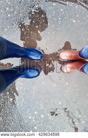 Mom And Daughter Are Walking In Rubber Boots Through The Puddles In Autumn