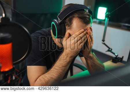 Angry devastated young man gamer wearing headphones lost a game on computer